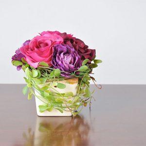Detalle recipiente cristal con rosas de diferentes tonos